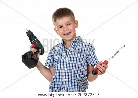 Smiling boy builder in checkered shirt holds a drill and a screwdriver in his hands, isolated on white background.