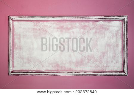 White empty antique frame made of gypsum in the Renaissance style. The wall is pink. Moldings. Background.
