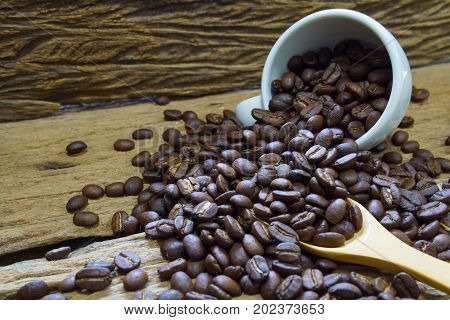 Pile Of Medium Or Dark Roasted Coffee Beans And White Cup With Wooden Spoon On Old Wooden Plank. Cof