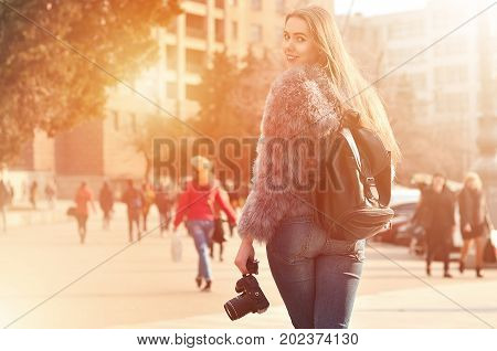 Rear View Of A Girl With A Digital Camera On A Crowded Street Background