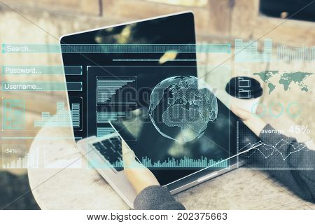 Side view of man hands using laptop and tablet with digital business hologram placed on wooden cafe table with coffee cup. Freelance and innovation concept. Double exposure
