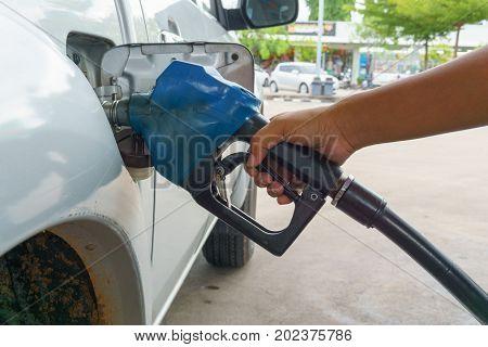 man hand holding petrol pump nozzle at gas station