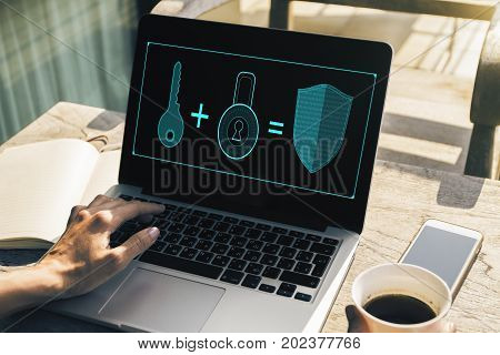Female hands using laptop with antivirus interface on screen and holding coffee cup placed on cafe table with other items. Shield concept