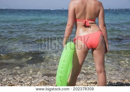 wet woman standing by the sea in a pink swimsuit with green life preserver