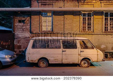 Old car with flat tire on the road. Outdoors photo.