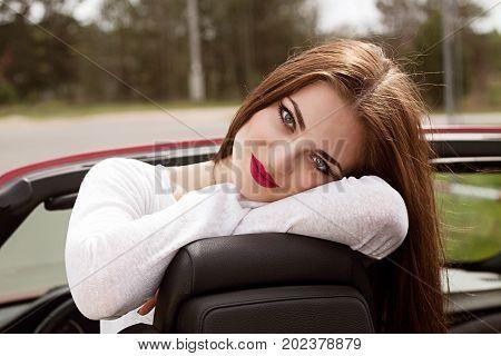 young pretty brunette girl in cabrio in spring