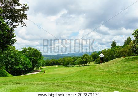 Golfer Walking With Caddies In Golf Course With View Of Mountain And Blue Sky And Cloud In Sunny Day