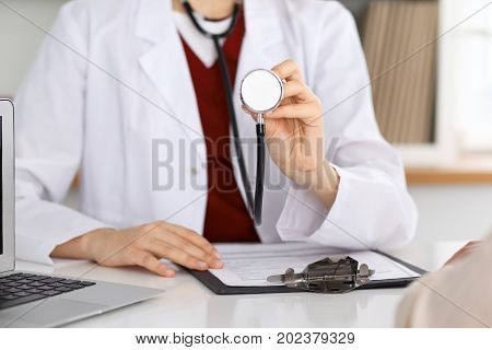 Unknown female doctor with a stethoscope in the hands. Physician is redy to exemine a patient. Medicine and health care conept
