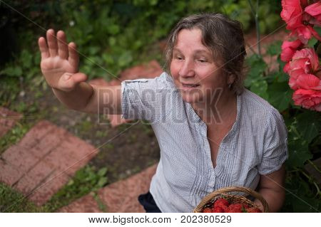Cheerful mature woman sits in the garden and waving to friends or neighbour