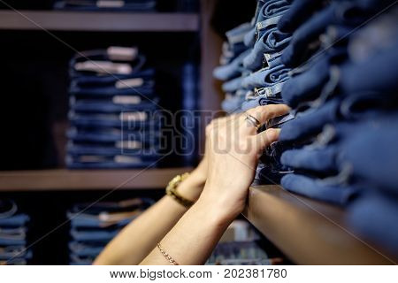 Seller in jeans store checking size of jeans