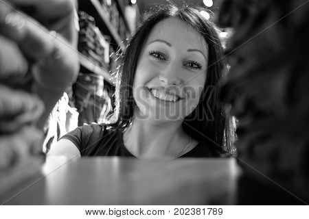 woman seller in jeans store looking through the shelf with clothes, monochrome
