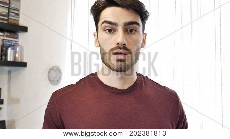 Young Handsome Man Looking Down Sad with Pouting Lips, Looking at Camera Indoor at Home