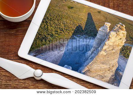 Castle Rock  - limestone pillar landmark in prairie of western Kansas near Quinter, revieing aerial image on a digital tablet
