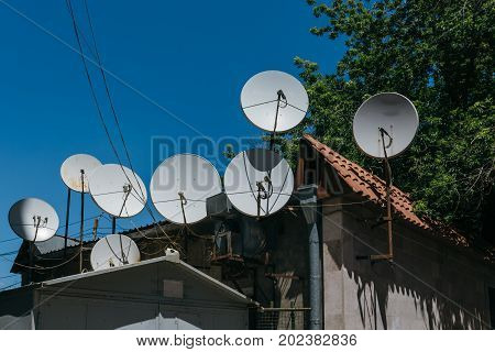 Many satellite dishes on the roof of a house on a sky background.