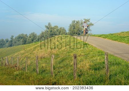 Unknown man cycling on top of a dike on a sunny day in the Dutch summer season.