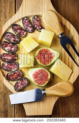 Spanish cured hard cheese cut in cubes sliced dry smoked sausage coated with black pepper crust fresh figs on wood platter. Simple traditional appetizer snack.