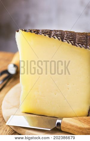 Wedge of Spanish goat cow and ewe cheese with black textured rind on wood cutting board. Special fork and knife on the table. Rustic kitchen interior. Close up copy space.