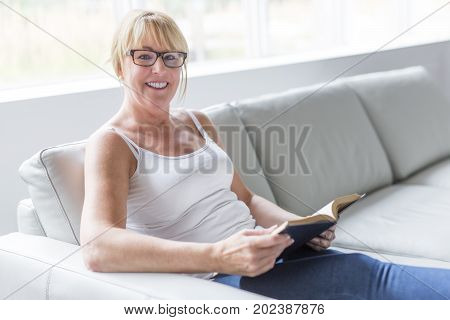 A Shot of a mature woman reading her favorite novel while at home in living room.