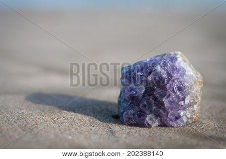 precious natural amethest gemstone on the sand