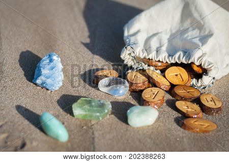 wood handmade runes and minerals on the sand poster