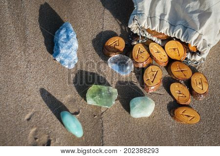 wood handmade runes and minerals on the sand