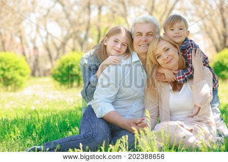 Cute happy children with grandparents in spring park on sunny day