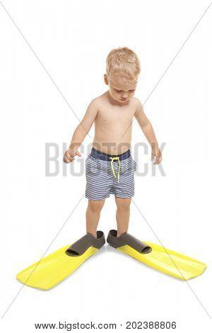 Cute little boy in blue striped swim trunks wearing bright yellow flippers on white background