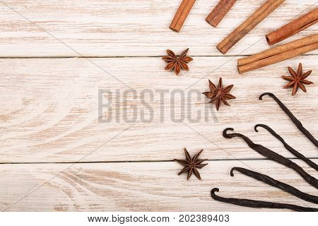 vanilla sticks, cinnamon, coffee beans and star anise on white wooden background with copy space for your text. Top view.