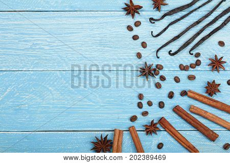 vanilla sticks, cinnamon, coffee beans and star anise on blue wooden background with copy space for your text. Top view.