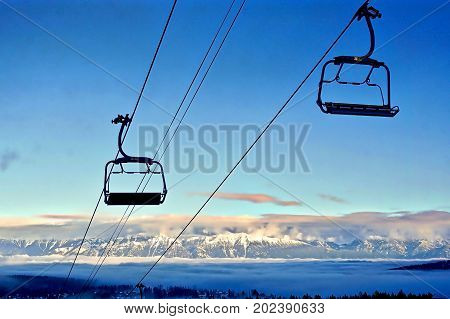 Empty ski lift chairs with snowy mountain background
