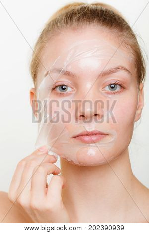 Beauty skin care cosmetics and health concept. Young woman face girl removing facial peel off mask. Peeling.