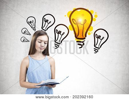 Portrait of a teen girl wearing a blue dress and holding an open book. She is reading while standing near a concrete wall with a many light bulb sketches.