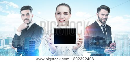 Three business partners two men and a woman are standing together and portraying success in a morning city. A woman is showing a tablet computer to the viewer. Toned image double exposure mock up