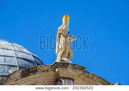 Statue of Saint Blaise on top of the facade of the baroque Church of St. Blaise in the old city of Dubrovnik. The saint shows in his left hand a scale model of the Romanesque church which was destroyed by the earthquake in 1667.