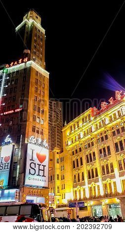 Shanghai, China - Nov 5, 2016: Night scene along Nanjing Road Pedestrian Street - Buildings with colorful lights in western architectural designs. People walking the street.
