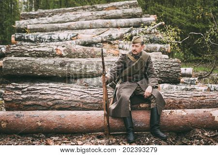 Pribor, Belarus - April 23, 2016: Re-enactor Dressed As Russian Soviet Infantry Red Army Soldier Of World War Ii Resting On Wooden Logs During A Campaign In Forest