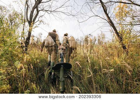 Two Reenactors Dressed As Russian Soviet Red Army Soldiers Of World War II Walking With With Maxim's Machine Gun Weapon In Autumn Meadow, Forest