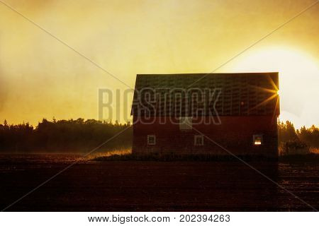 Sunrise over an old red wooden barn. Texture effect added.