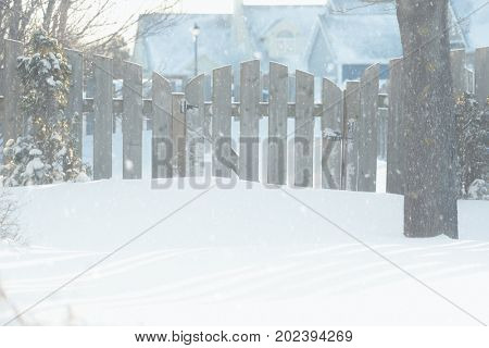 Snow falling near a garden gate in a residential neighborhood.