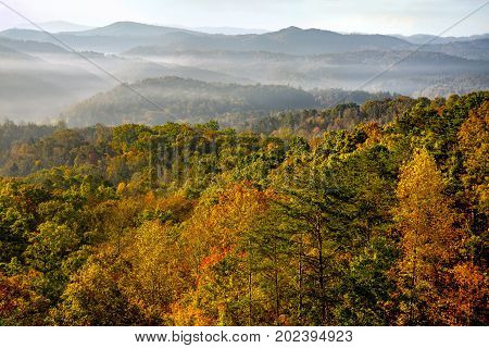 The sun rises over the mountains of Great Smoky Mountains National Park at the peak of autumn's colors. This is looking east into the Smoky mountains from the Foothills Parkway West.