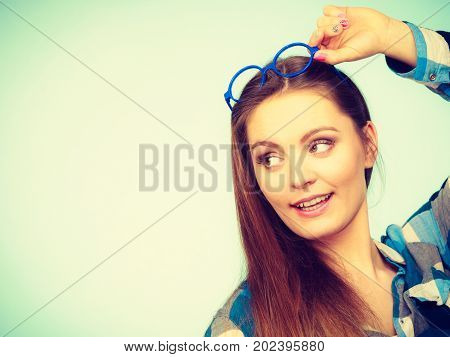Studying beauty of education and fun concept. Attractive nerdy woman in weird big glasses on head. Studio shot on blue background