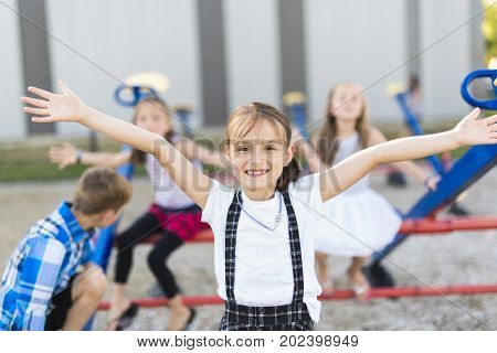 Some cheerful school age child play on playground school