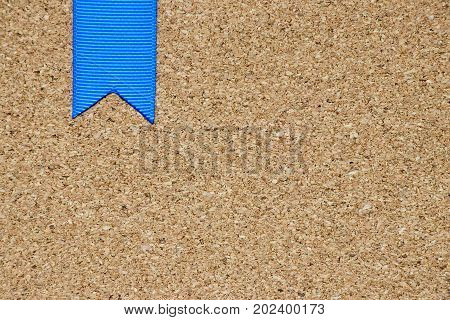 Blue ribbon placed on cork board background with the space for add text
