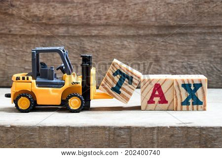 Toy plastic forklift hold block T to compose and fulfill wording TAX on wood background