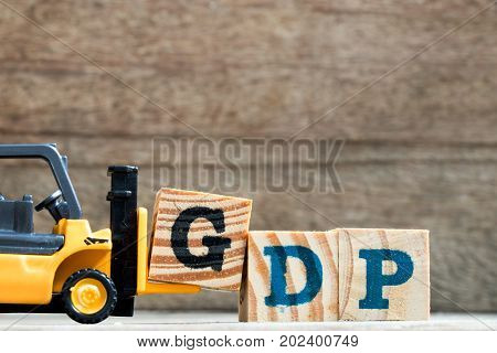 Toy plastic forklift hold block G to compose and fulfill wording GDP (Gross domestic product or Good distribution practice) on wood background