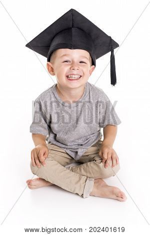 An Adorable four years old child boy wearing a mortar board.