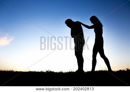 A Sad young man silhouette worried at sunset with woman help
