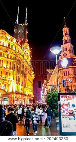 Shanghai, China - Nov 5, 2016: Night scene along Nanjing Road Pedestrian Street - Buildings with colorful lights in western architectural designs. People walking on the street.