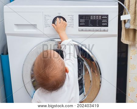 Curious Cute little Asian 18 months / 1 year old toddler baby boy child playing and turning on the washing machine Selective focus at baby hand