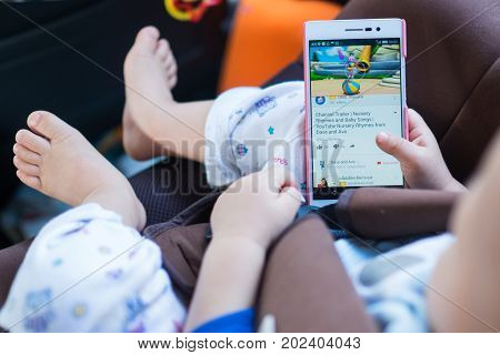Bangkok Thailand - FEB 13 2017: Asian toddler baby boy sitting in car seat and watching a video from Youtube on Huawei android smartphone. Bird eye view (Shallow depth of field & Selective Focus)